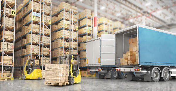 Freight trucks being loaded by forklift in a warehouse