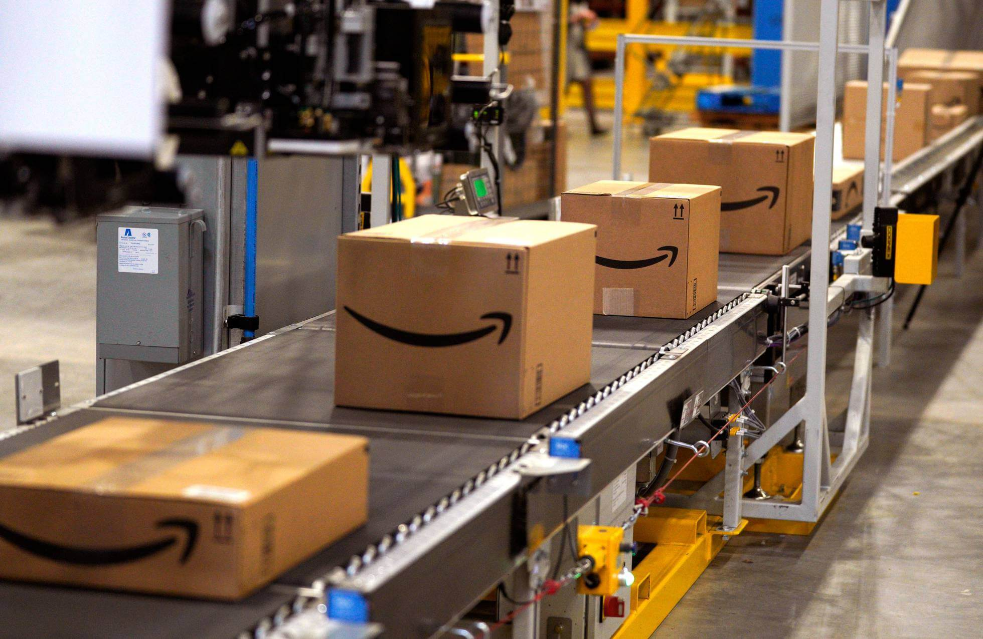 Amazon packages on a conveyer belt in a warehouse